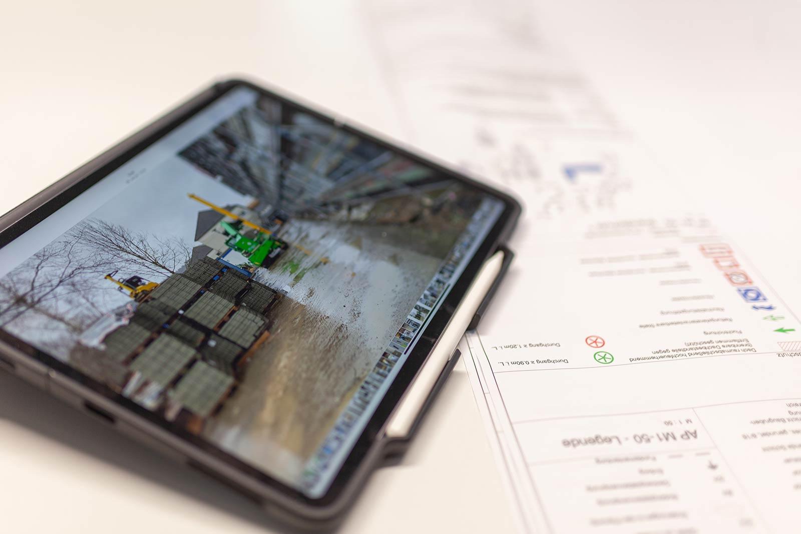Tablet mit Plänen und Fotos